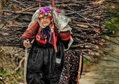 Old woman carrying heavy bundle of wood